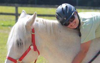 women hugging horse